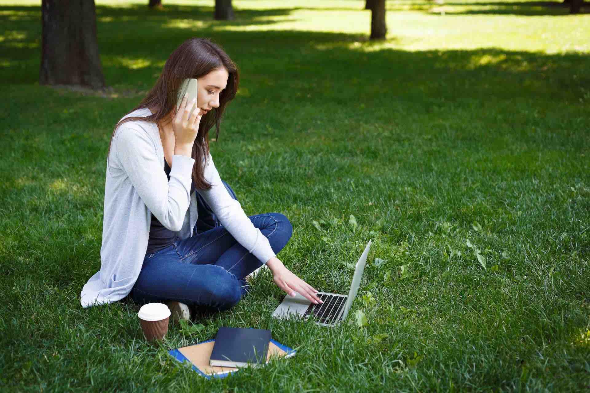 Frau_im_Park_auf_Rasen_sitzend_mit_Smarthphone_und_Notebook