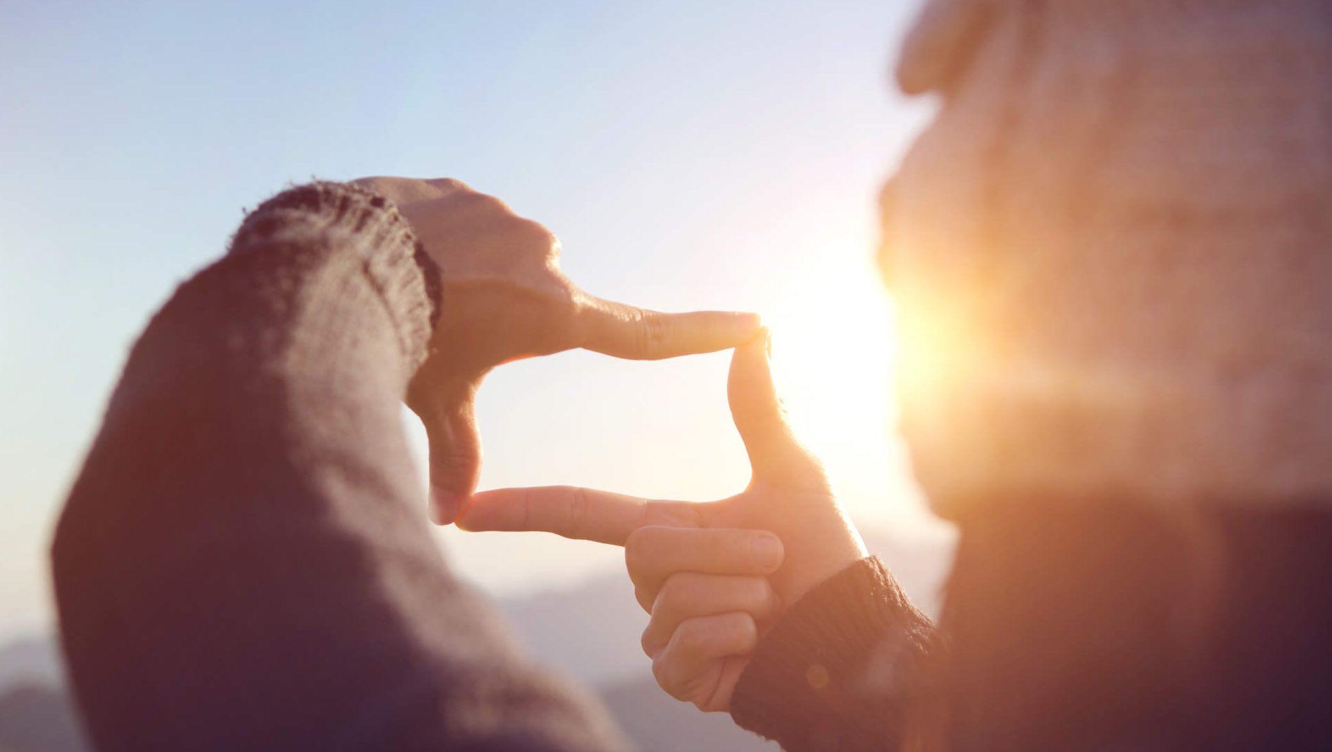 Frau_legt_ihre_Finger_auf_einem_Berg_in_einer_rahmenden_Geste_zusammen